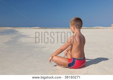 The Little Boy Meditating On The Beach