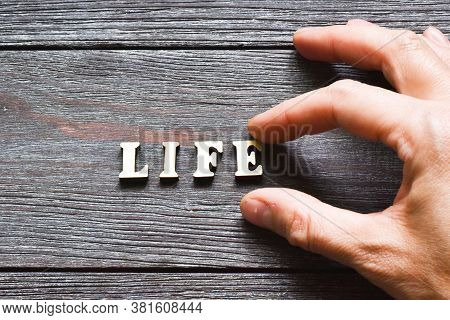 Female Hand Holding A Wooden Letter With The Inscription: Life On A Wooden Background. Safe Life. Pr