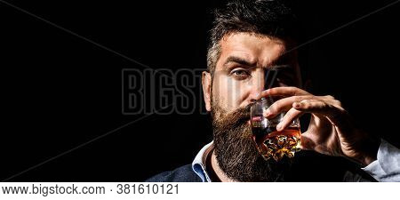 Man With Beard Holds Glass Brandy. Bearded Drink Cognac. Sommelier Tastes Drink. Man Holding A Glass