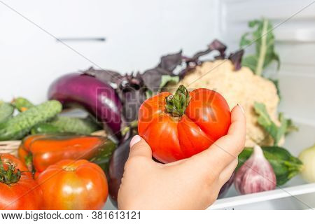 Woman Taking Fresh Tomato From The Refrigerator At Home, Woman Takes Tomato From The Open Refrigerat