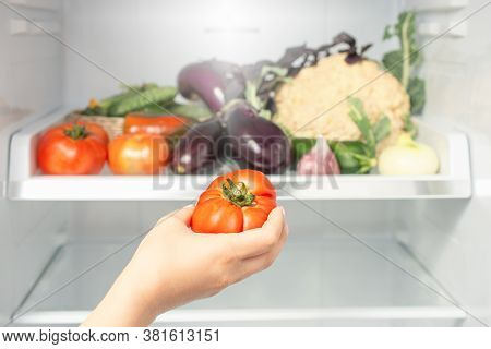 Concept Of Healthy And Dieting Food. Woman's Hand Takes Tomato From The Refrigerator Shelf. Healthy