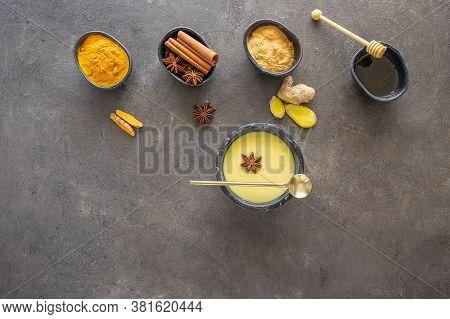Top View Of Golden Milk Ayurvedic Warm Beverage In Black Mug And Ingredients On Concrete Background.