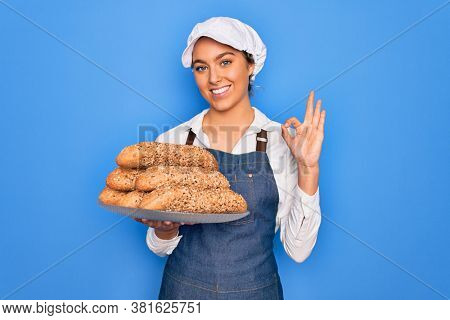 Young beautiful blonde baker woman with blue eyes holding tray with wholemeal bread cereal doing ok sign with fingers, excellent symbol