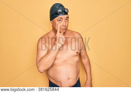 Middle age senior grey-haired swimmer man wearing swimsuit, cap and goggles Pointing to the eye watching you gesture, suspicious expression