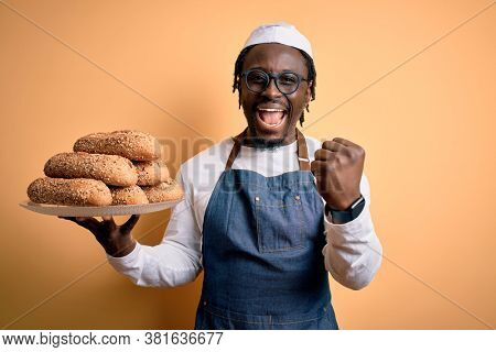 Young african american bakery man holding tray with healthy wholemeal bread screaming proud and celebrating victory and success very excited, cheering emotion