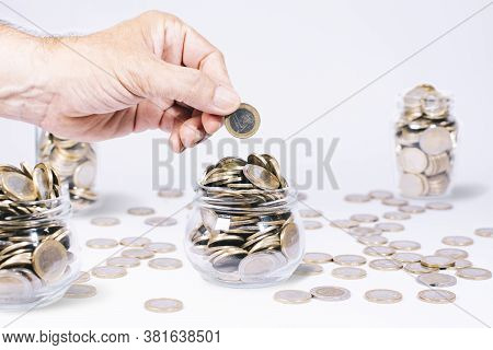 Male Hand With A Euro Coin On A Glass Jar Full Of Euro Coins, Other Defocused Glass Jars And Euro Co