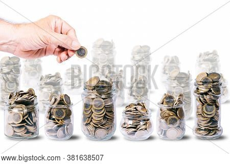 Male Hand With One Euro Coin Over Several Glass Jars Full Of Euro Coins, Other Glass Jars Out Of Foc