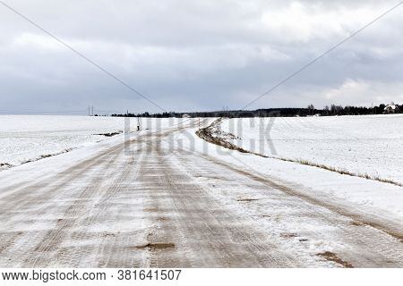 Winter Time On A Narrow Rural Highway, The Road Is Covered With Snow After Snowfall And Built In, Fr