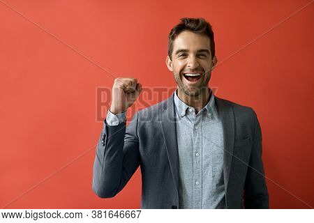 Ecstatic Businessman Cheering In Front Of A Red Background
