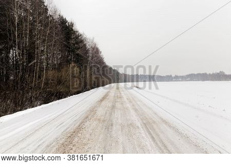 Winter Time On A Narrow Road In The Forest, The Road Is Covered With Snow After Snowfall, Frosty Wea