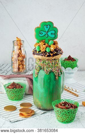 St. Patricks Freak Shake Topping With Clover Cookie And Chocolate Cupcakes On Grey Background