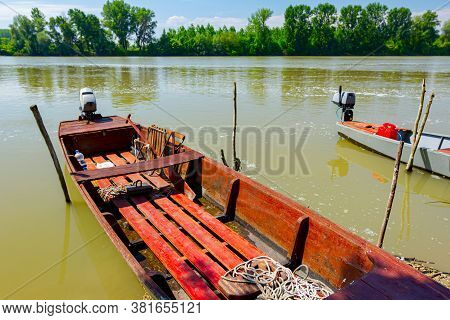 Red Wooden Fishing Boat Anchored On Improvised Dock On The River.