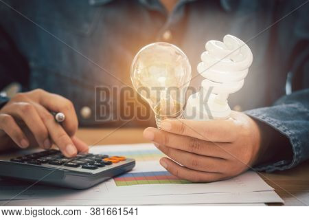 The Hand Was Holding An Incandescent Light Bulb And A Spiral Light Bulb And Pressing The Calculator