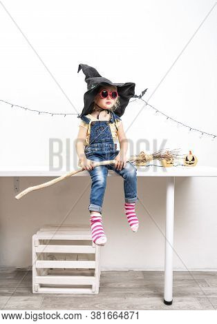 Happy Halloween: A Little Girl Sits On A Table In A Witch Hat With A Broom.