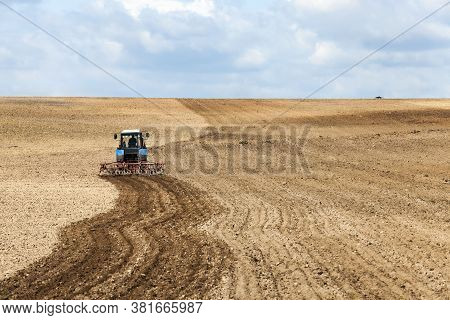 A Half Plowed Agricultural Field Where Wheat Was Harvested And A Tractor Ploughed The Remaining Stub