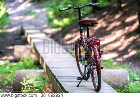 The Bike Is On The Running Board. Wooden Bridge Over The Ravine. A Rest Stop, The Concept Of A Count