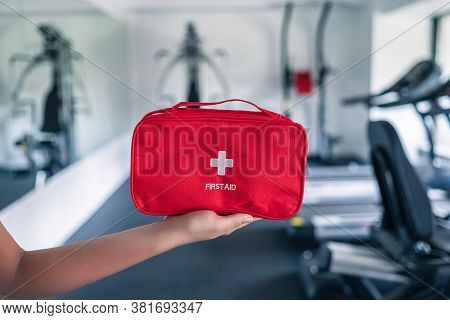First Aid Kit Red Box In Instructor Female Hand In Fitness Gym Opposite The Sport Equipment And  Jog