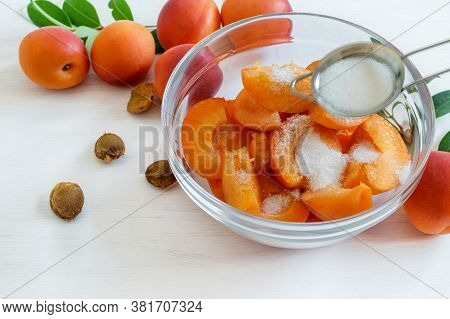 Slices Of Ripe Apricots Sprinkling With Sugar In The Transparent Glass Bowl. Cooking Homemade Jam.