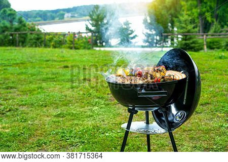 Barbecue Time At The Nature. Bbq Grilling On The Shore Of A Picturesque Lake. Copy Space.