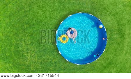 Aerial. Girl Swims In A Metal Frame Pool With Inflatable Toys. Frame Pool Stand On A Green Grass Law