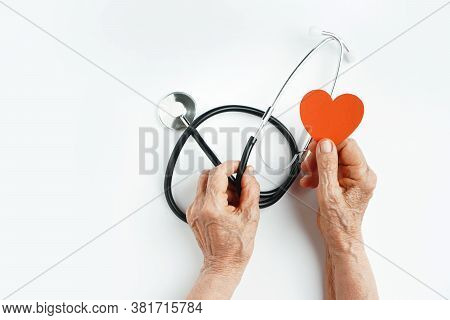 Elderly Wrinkled Hands Holds A Stethoscope And Heart Symbol. Heart Care In Old Age Concept.