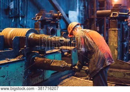 Heavy Industry Worker Working Hard On Machine. Rough Industrial Environment