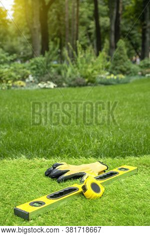 Artificial Grass Laying Background With Work Tools On A Beautiful Garden Backdrop.