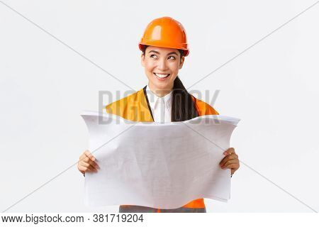 Creative Asian Female Architect Imaging Her Plan, Standing In Safety Helmet And Looking Away Thought