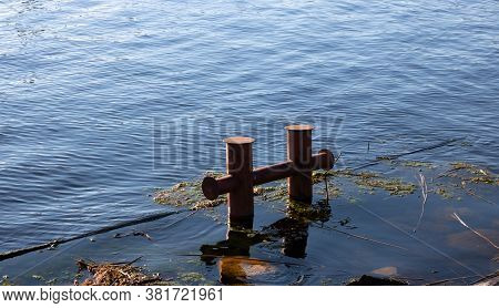 An Old Red Double Round Rusty Mooring Bollard On A Flooded River Pier