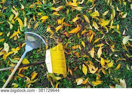 Rake And Broom Lying On The Yellow Fallen Leaves In The Fall. Gardening During The Fall Season. Clea