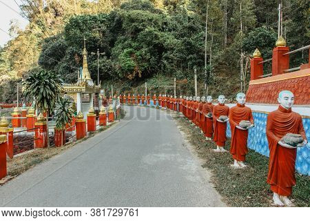 Row Of Statues Of Buddhist Monks Close To A Popular Tourist And Religious Cave Entrance Near The Cit