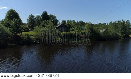 Village With Wooden House Built On The Shore Of A Pond. Shot. Ecological Place For Living, Small Hou