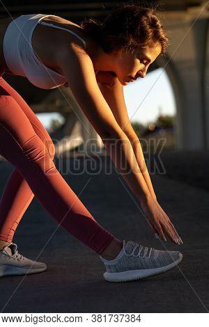 Slim Sportswoman In Pink Leggings Standing Under The Bridge At Sunset, Stretching Muscles Making Fun