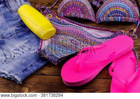Set Of Beachwear On Wooden Background. Sunscreen, Swimsuit, Jean  Shorts And Flip-flops. Summer Holi