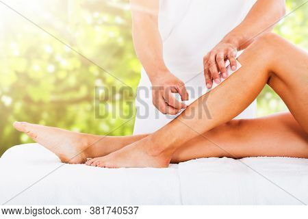 Midsection Of Beautician Waxing Woman's Leg With Wax Strip At Beauty Spa