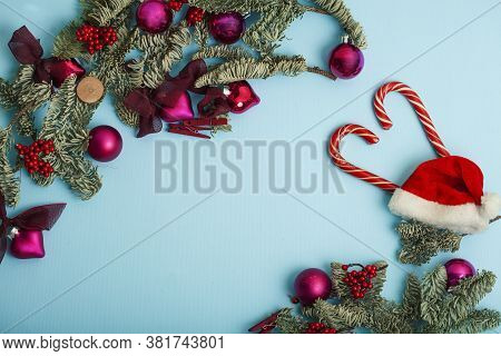 Christmass Stuff Laying Flat On Colorful Background, Branch Of Tree, Balls, Candy