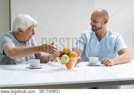Caretaker In Retirement Home With Elder Man