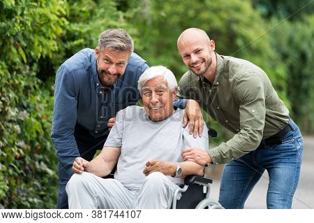 Old Disabled Grandfather In Wheelchair With Caring Family