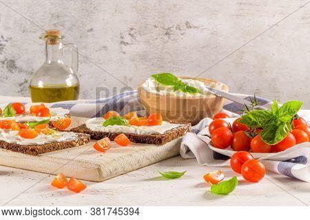 Rye Bread Bruschetta With Cream Cheese, Olive Oil And Basil Dip, Cherry Tomatoes, Fresh Basil Leaves