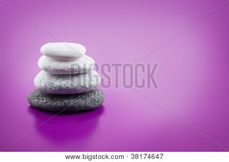 Assorted Balanced Stones On Purple Background With Copy Space