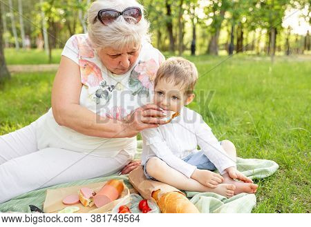 Grandmother And Cute Grandson Are Having Lunch Along On Summer Grass In The Green Park Together. Gra