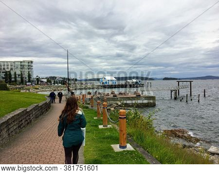 Sidney, British Columbia, Canada - July 1st, 2020: People Walking Along The Boardwalk Overlooking Th
