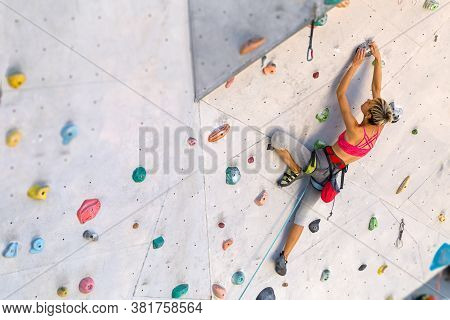 A Woman Climbs A Climbing Wall, A Climber Is Training On Artificial Terrain, Rock Climbing In The Ci