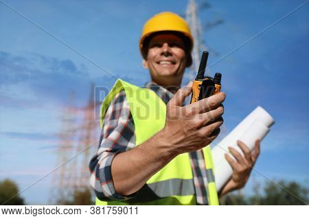 Professional Electrician Near High Voltage Tower, Focus On Hand With Portable Radio Station