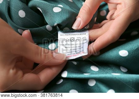 Woman Reading Clothing Label With Care Instructions And Content Information On Green Polka Dot Garme