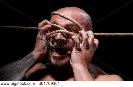Image Of Binded Screaming Bald Man With Rope On Face