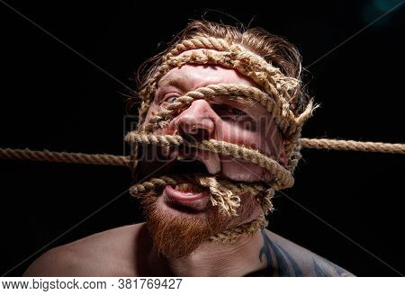 Portrait Of Binded Tattooed Screaming Man With Rope On Face