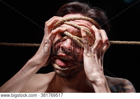 Image Of Binded Brunette Man Trying Tear The Rope On Face