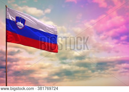 Fluttering Slovenia Flag Mockup With The Place For Your Text On Colorful Cloudy Sky Background.