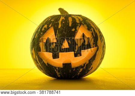 Happy Halloween. Funny Glowing Pumpkin Jack-o-lantern On A Yellow Background. Backlight